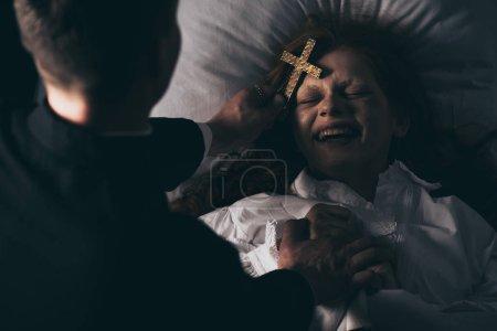 Photo pour Exorciste tenant croix sur rire démon au lit - image libre de droit