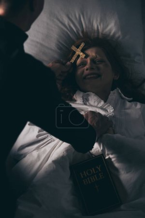 Photo for Exorcist with bible and cross standing over demoniacal girl in bed - Royalty Free Image