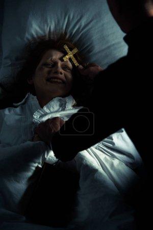 Photo pour Exorciste tenant croix sur femme démon au lit - image libre de droit