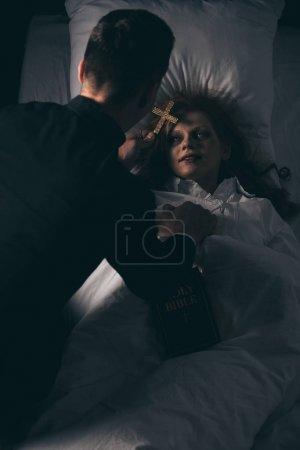 Photo pour Exorciste avec bible et croix debout sur fille obsédée au lit - image libre de droit