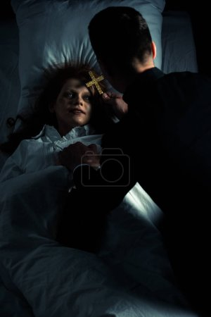 Photo for Exorcist holding cross over female creepy demon in bed - Royalty Free Image