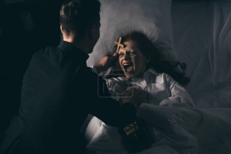 Photo for Male exorcist with bible and cross standing over demoniacal screaming girl in bed - Royalty Free Image