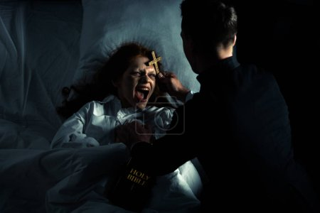 Photo for Exorcist with bible and cross standing over demoniacal yelling girl in bed - Royalty Free Image