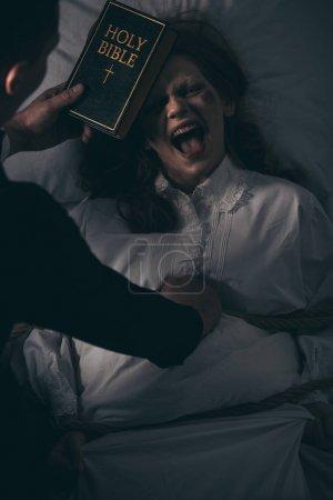 Photo pour Exorciste avec bible et obsédé femme hurlante dans la chambre - image libre de droit