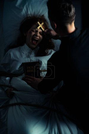 Male exorcist with bible and cross standing over d...