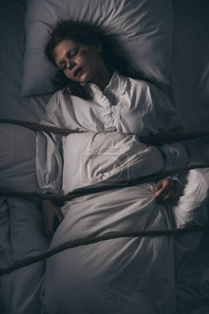 Photo for Demonic obsessed sleeping girl in nightgown bound with rope in bed - Royalty Free Image