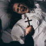 Exorcist holding cross over creepy screaming demon...