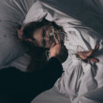 Exorcist holding cross over female demon in bed...
