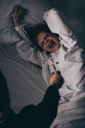 Photo pour Exorciste tenant croix sur effrayant cris démon dans le lit - image libre de droit