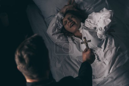 Photo for Exorcist holding cross over demonic screaming girl in bed - Royalty Free Image