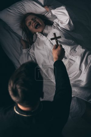 Photo for Exorcist holding cross over obsessed yelling girl in bed - Royalty Free Image