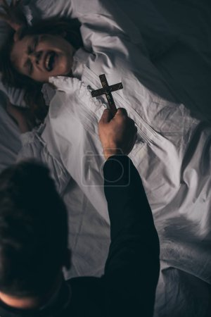 Photo for Exorcist holding cross over obsessed screaming girl in bed - Royalty Free Image