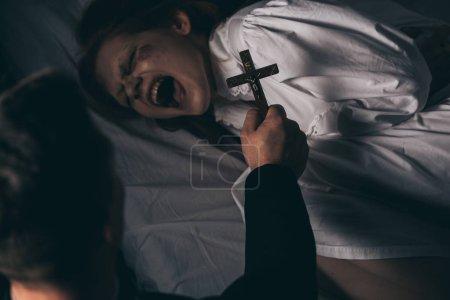 Photo pour Exorciste tenant croix sur démoniaque hurler fille dans lit - image libre de droit