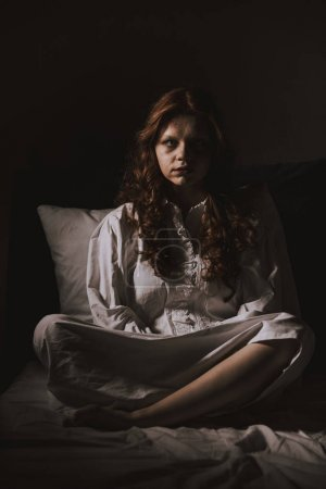 Photo for Demonic young woman in nightgown sitting in bed - Royalty Free Image