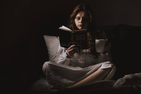 Demonic woman in nightgown holding cup and reading...