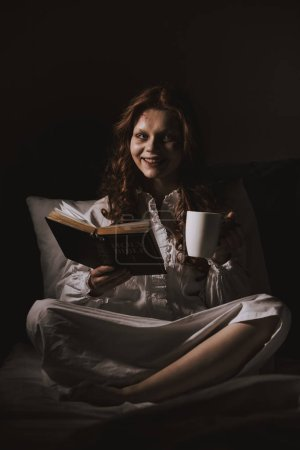 Photo pour Femme souriante démoniaque en chemise de nuit tenant bible et tasse sur le lit - image libre de droit
