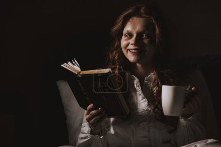 Demonic smiling girl in nightgown holding bible an...