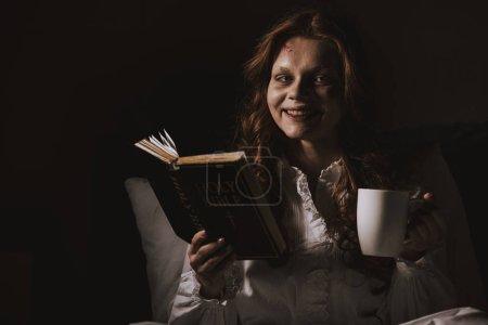 Photo pour Fille souriante démoniaque en chemise de nuit tenant bible et tasse sur le lit - image libre de droit