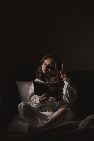 Demoniacal girl in nightgown reading bible and poi...