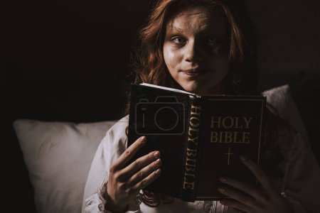 Creepy demoniacal girl in nightgown holding holy b...