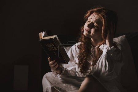 Creepy demoniacal crying woman reading holy bible ...