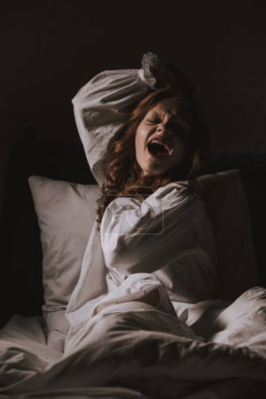 Paranormal gothic girl in nightgown yelling in bed...