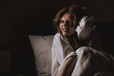 Female smiling devil in nightgown sitting in bed...