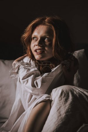 Demonic smiling girl in nightgown sitting in bed...
