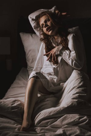 Paranormal obsessed young woman in nightgown sitti...