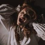 Demonic girl in nightgown shouting in bedroom...