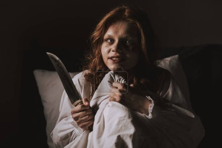Photo for Demoniacal girl in nightgown holding knife in bed - Royalty Free Image