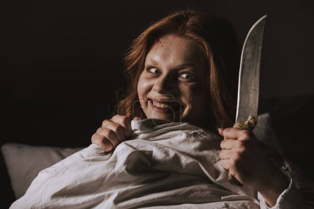 Photo for Demoniacal smiling girl holding knife in bed - Royalty Free Image