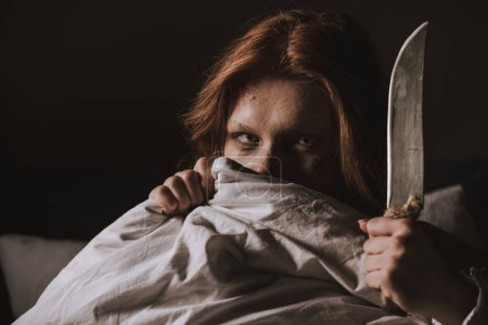 Photo for Demonic obsessed evil girl holding knife in bed - Royalty Free Image