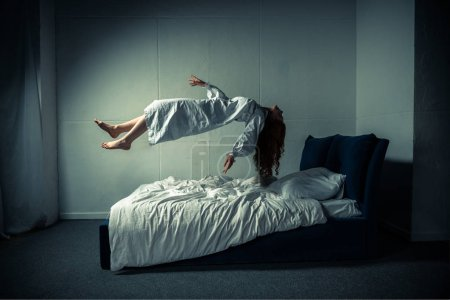 Photo for Creepy woman in nightgown sleeping and levitating over bed - Royalty Free Image
