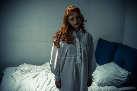 Photo for Creepy demonic girl in nightgown standing in bedroom - Royalty Free Image
