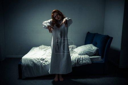 Photo pour Démon féminin effrayant en chemise de nuit debout dans la chambre - image libre de droit