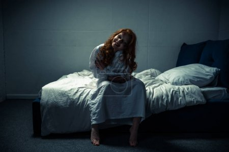 Photo for Crazy demoniacal smiling woman in nightgown sitting on bed - Royalty Free Image