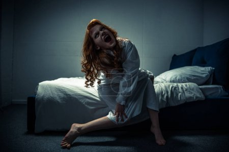 Photo for Demonic creepy girl in nightgown shouting in bedroom - Royalty Free Image