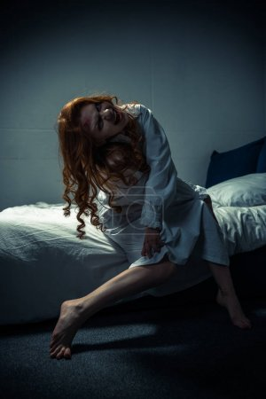 Photo for Demoniacal ghost in nightgown screaming in bedroom - Royalty Free Image