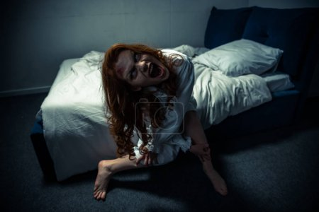 Photo for Demonic woman in nightgown screaming in bedroom - Royalty Free Image