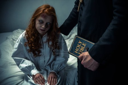 Photo for Exorcist holding bible and hugging demoniacal girl in bedroom - Royalty Free Image