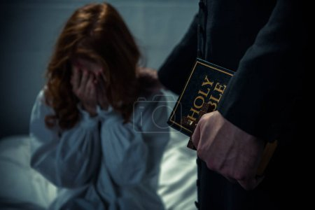 Photo for Exorcist holding bible and hugging crying girl in bedroom - Royalty Free Image