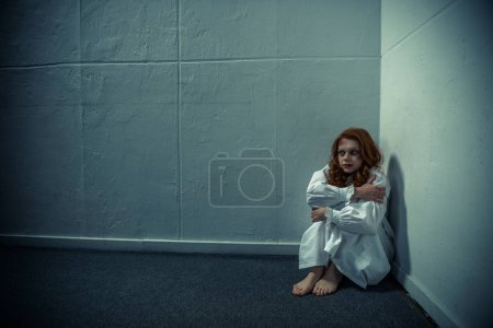 Evil girl in nightgown standing near wall...