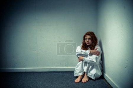 Photo pour Fille démoniaque mal en chemise de nuit debout près du mur - image libre de droit