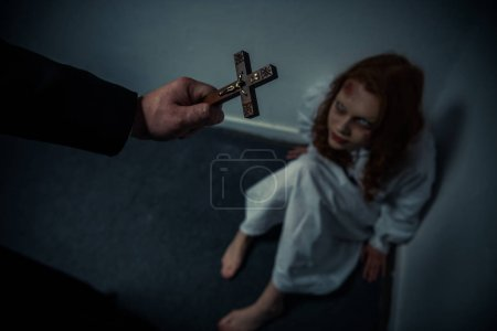 Photo for Exorcist holding cross in front of obsessed girl - Royalty Free Image