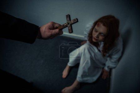 Photo pour Exorciste tenant croix en face de fille obsédée - image libre de droit
