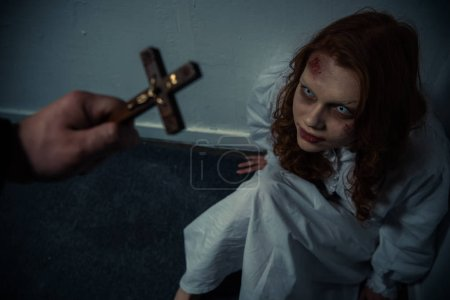 Exorcist holding cross in front of obsessed girl...