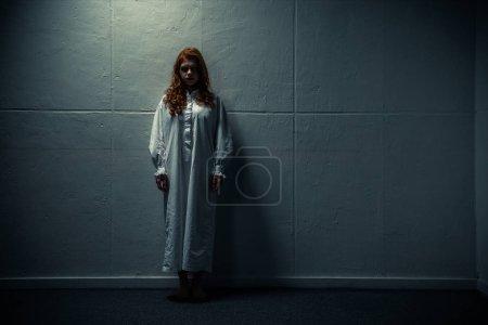 Photo pour Fille obsédée démoniaque en chemise de nuit debout près du mur - image libre de droit
