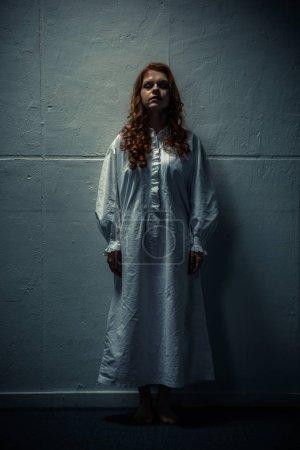 Photo pour Femme démoniaque en chemise de nuit debout près du mur - image libre de droit