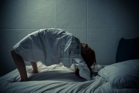 Photo for Obsessed demonic girl in nightgown standing on legs and arms on bed - Royalty Free Image